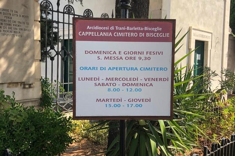 Cartello indicante gli orari di apertura del cimitero di Bisceglie